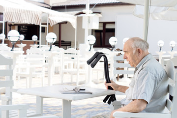 Disabled man sitting at an outdoor restaurant