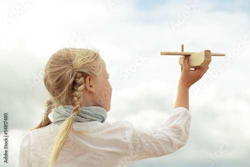 Girl and airplane toy on the cloudy sky background