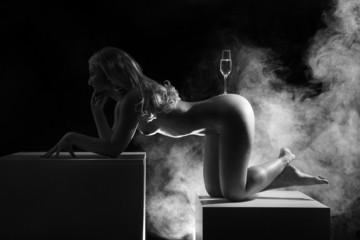 Nackte Frau auf Würfel balanciert Sektglas auf Po