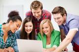 international students looking at laptop at school