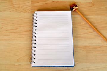 Libreta y lápiz sobre escritorio de madera