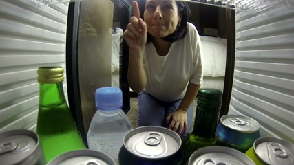 woman opening the fridge. Taking something to drink very happy