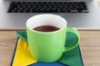 Green cup on napkin on laptop background on wooden table