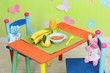 Tasty baby fruit puree and baby bottle on table in room