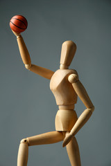 Wooden mannequin with basketball ball on grey background