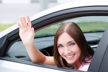 Woman driver smiling and greeting you by hand