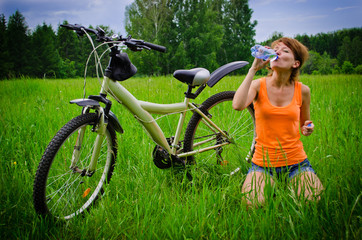Young woman drinking water on grass