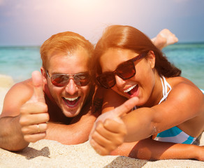 Happy Couple in Sunglasses having fun on the Beach