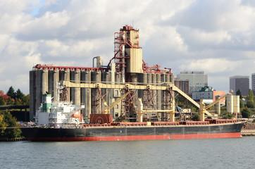 Large grain ship next to a silo loading facility