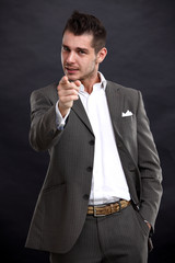 young business man pointing to the camera on black background