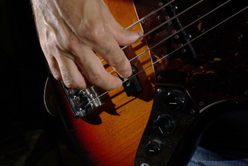 Man playing an bass guitar with brown body