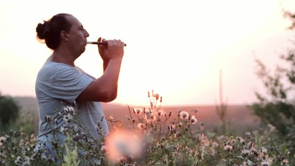 flutist playing at sunset, a musician playing a flute (sunset)