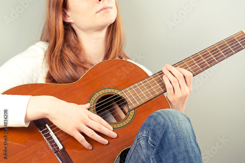 Woman with a classical guitar making music