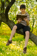 Handsome teenage boy sitting on the tree and reading old book