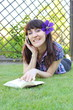 Smiling woman with book and mobile phone in sunny garden