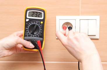Hand's electrician with multimeter checking voltage