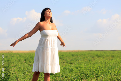 Young happy woman breathing fresh air in green field