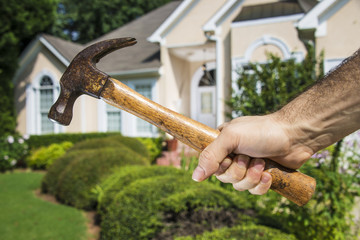 Hand Holding Hammer in front of House
