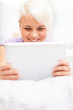 Smiling woman in the bed with tablet pc