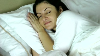 woman sleeping on her bed at home having a very happy dream