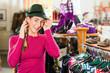 Frau kauft Trachtenhut zum Dirndl in einer Boutique