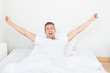 Man Waking Up In Morning And Stretching On Bed