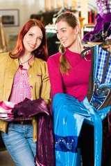 Ein Frau mit Freundin kauft Tracht oder Dirndl in einer Boutique