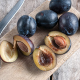 plums on a wooden kitchen board