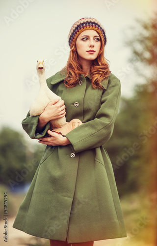 Redhead girl with duck at outdoor