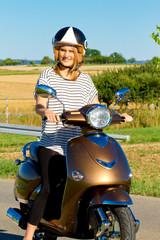 Junge Frau auf dem Motorroller