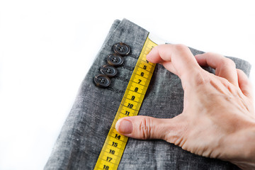 Tailor hand measuring with tape a man suit