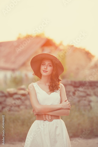 Redhead girl at outdoor. Old country house at background.