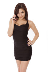 Young woman in a little black dress talks on the phone.