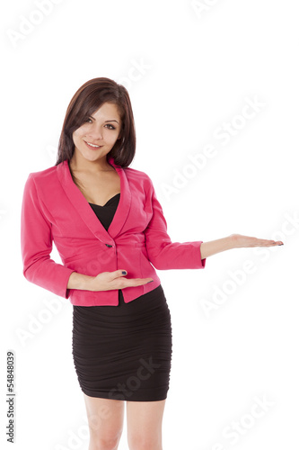Young woman in business outfit gestures towards a product.
