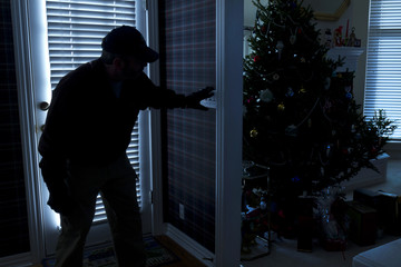 Burglar Breaking In To Home At Christmas Through Back Door