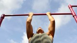 Athlete pulls on the bar. Pullups