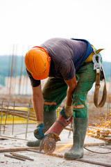 Builder worker sawing metal at construction site
