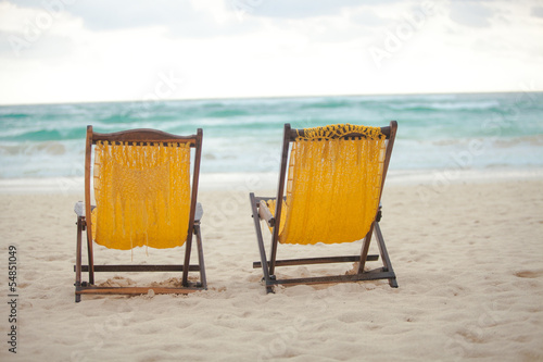 Beach yellow chairs for vacations on tropical beach in Tulum, © travnikovstudio