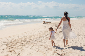 Back view of young mother and her cute daughter walking on