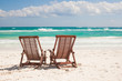 Beach wooden chairs for vacations on tropical beach in Tulum,