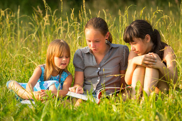 Three cute little girls reading book in natural environment