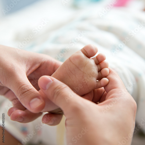 massaging little baby's foot