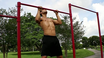 handsome athletic guy pulls on the bar. Pull ups