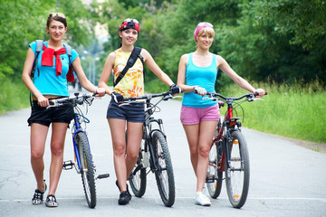 Young pretty women  walk  with  bicycle