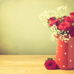 Rose flower bouquet in red polka dots jug with copy space