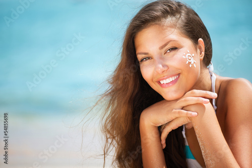 Beautiful happy Girl applying Sun Tan Cream on her Face