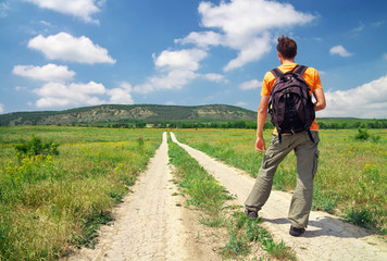 Man with a backpack on a country road. Man tourist. Leisure acti