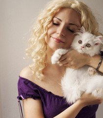 Beautiful young woman holding white Persian kitten