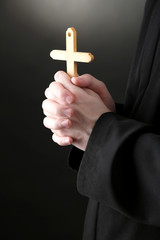 Priest holding cross, on black background