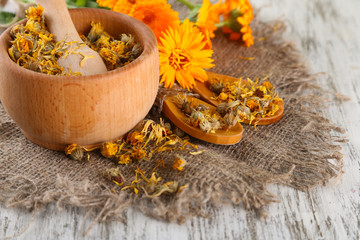 Fresh and dried calendula flowers in mortar on wooden